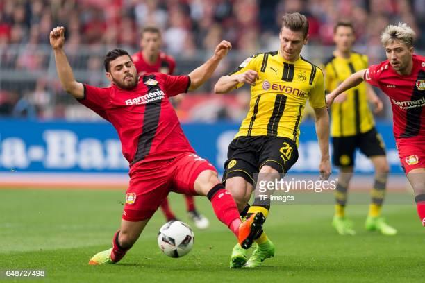 Kevin Volland of Bayer Leverkusen and Lukasz Piszczek of Dortmund battle for the ball during the Bundesliga match between Borussia Dortmund and Bayer...