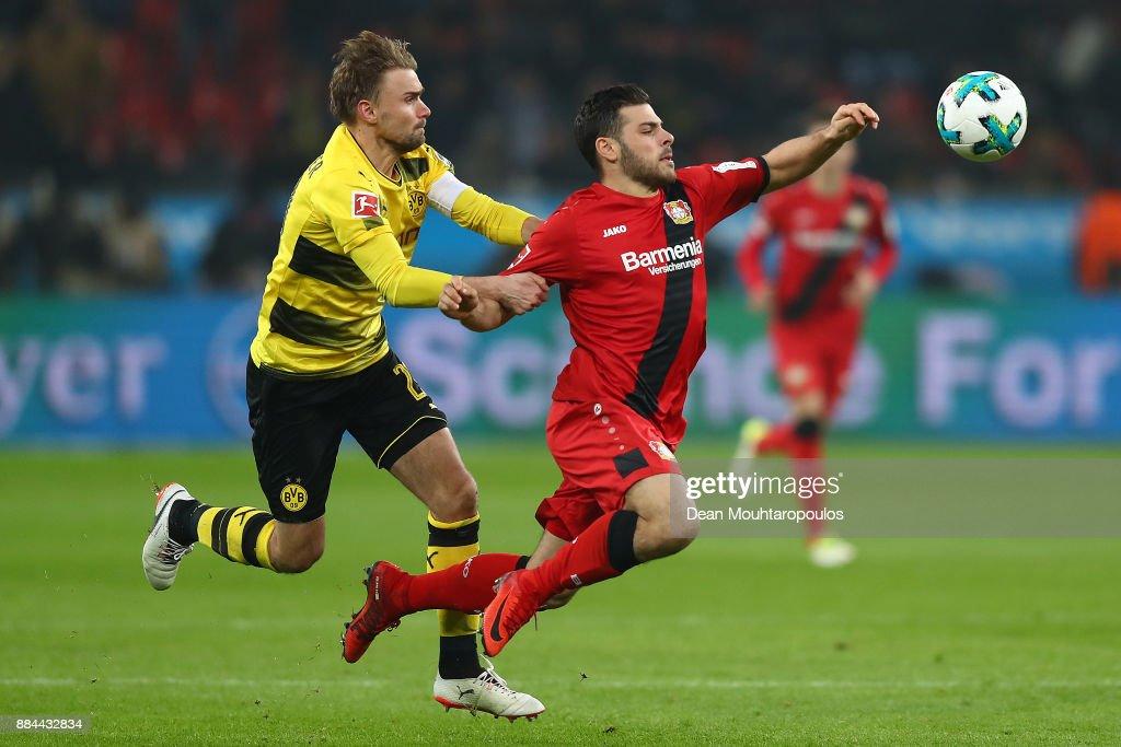 Kevin Volland of Bayer Leverkusen (r) is fouled by Marcel Schmelzer of Dortmund during the Bundesliga match between Bayer 04 Leverkusen and Borussia Dortmund at BayArena on December 2, 2017 in Leverkusen, Germany.