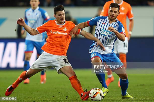 Kevin Volland of Hoffenheim is challenged by Jerome Gondorf of Darmstadt during the Bundesliga match between 1899 Hoffenheim and SV Darmstadt 98 at...