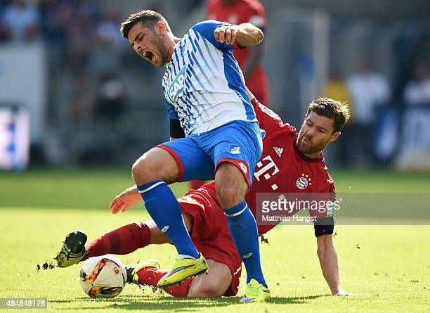 Kevin Volland of Hoffenheim is challenged by Xabi Alonso of Muenchen during the Bundesliga match between 1899 Hoffenheim and FC Bayern Muenchen at...