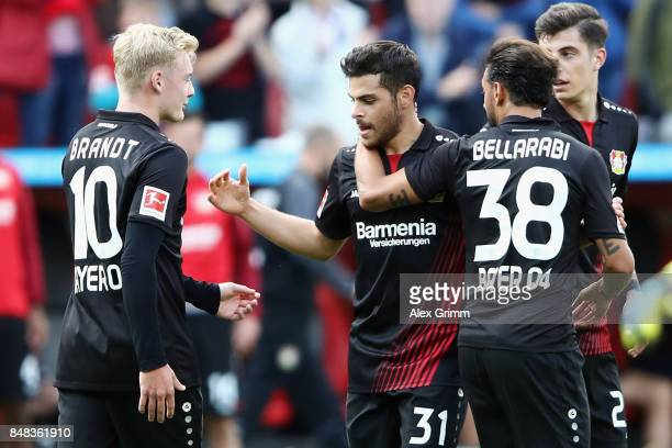 Kevin Volland of Leverkusen celebrates his team's third goal with team mates Julian Brandt and Karim Bellarabi during the Bundesliga match between...