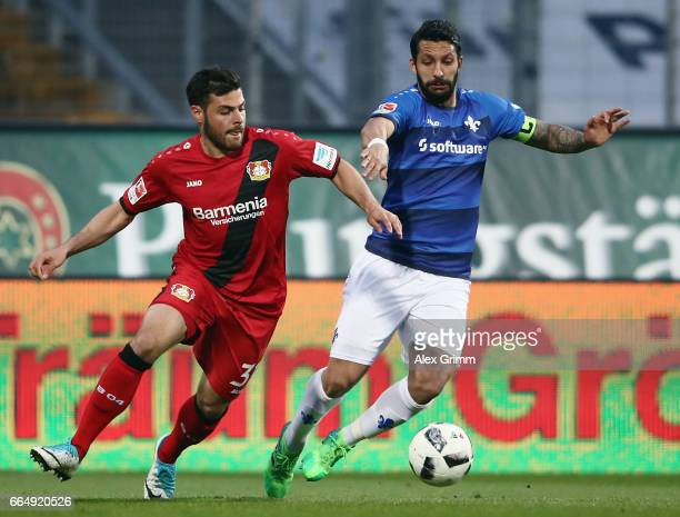 Kevin Volland of Leverkusen is challenged by Aytac Sulu of Darmstadt during the Bundesliga match between SV Darmstadt 98 and Bayer 04 Leverkusen at...
