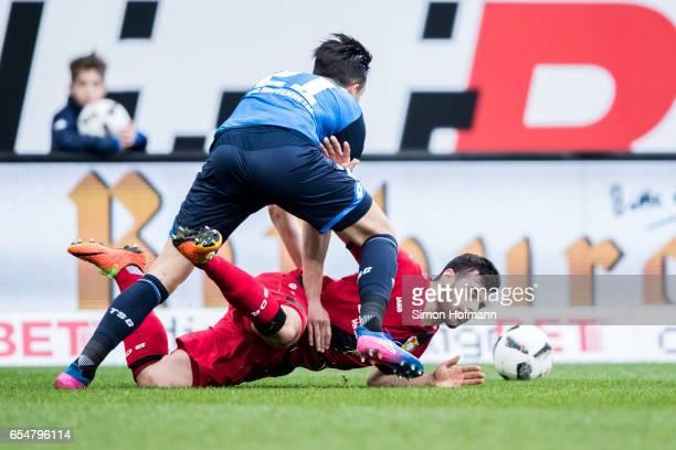 Kevin Volland of Leverkusen is challenged by Benjamin Huebner of Hoffenheim during the Bundesliga match between TSG 1899 Hoffenheim and Bayer 04...