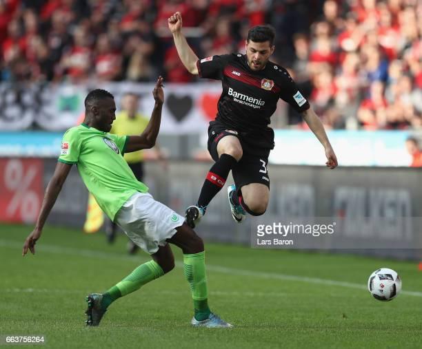 Kevin Volland of Leverkusen is challenged by Josuha Guilavogui of Wolfsburg during the Bundesliga match between Bayer 04 Leverkusen and VfL Wolfsburg...