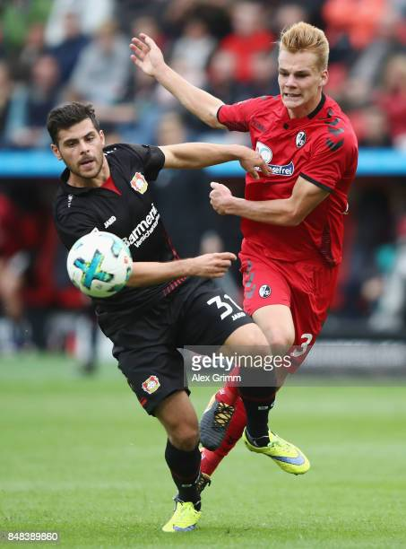 Kevin Volland of Leverkusen is challenged by Philipp Lienhart of Freiburg during the Bundesliga match between Bayer 04 Leverkusen and SC Freiburg at...