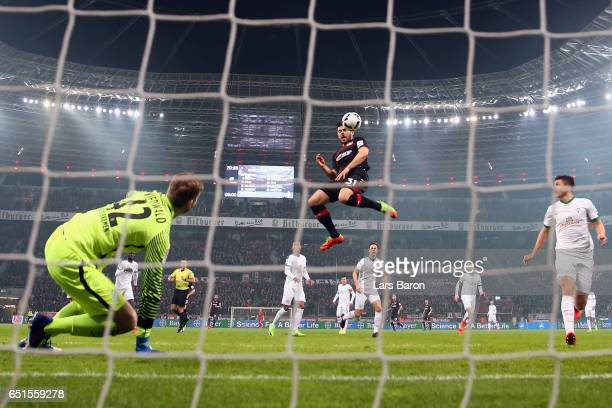 Kevin Volland of Leverkusen scores his team's first goal past goalkeeper Felix Wiedwald of Bremen during the Bundesliga match between Bayer 04...