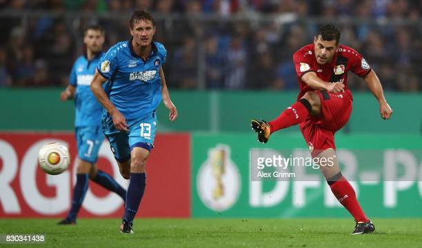 Kevin Volland of Leverkusen takes a shot on the past Kai Buelow of Karlsruhe during the DFB Cup first round match between Karlsruher SC and Bayer...