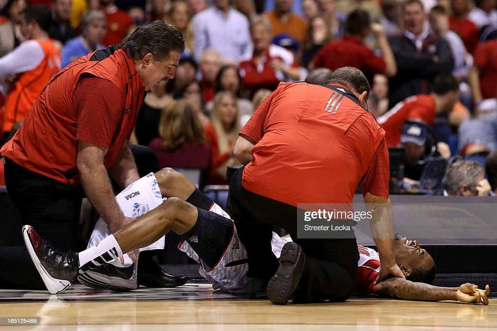 Kevin Ware #5 of the Louisville Cardinals is tended to by medical personnel after he injured his leg in the first half against the Duke Blue Devils during the Midwest Regional Final round of the 2013 NCAA Men's Basketball Tournament at Lucas Oil Stadium on March 31, 2013 in Indianapolis, Indiana.