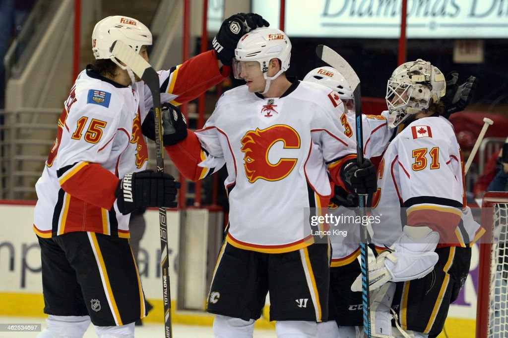 Kevin Westgarth Ladislav Smid and Karri Ramo of the Calgary Flames celebrate following their game against the Carolina Hurricanes at PNC Arena on...
