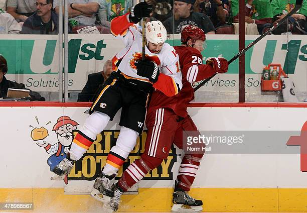 Kevin Westgarth of the Calgary Flames checks Michael Stone of the Phoenix Coyotes along the boards during the first period at Jobingcom Arena on...
