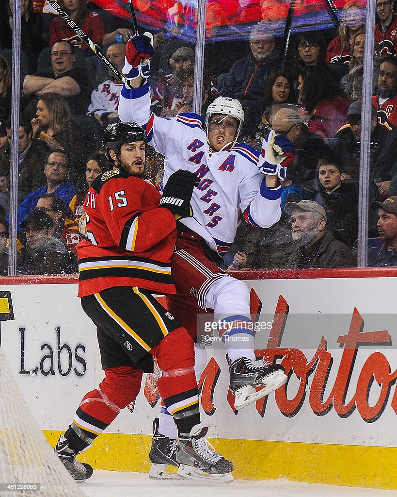 Kevin Westgarth #15 of the Calgary Flames shoves Marc Staal #18 of the New York Rangers during an NHL game at Scotiabank Saddledome on March 28, 2014 in Calgary, Alberta, Canada.