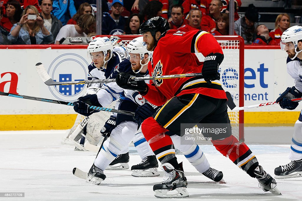 Kevin Westgarth #15 of the Calgary Flames skates against Matt Halischuk #15 of the Winnipeg Jets at Scotiabank Saddledome on April 11, 2014 in Calgary, Alberta, Canada.