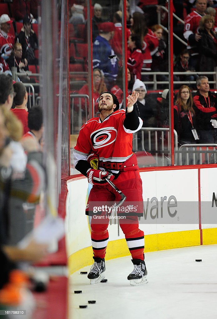 Kevin Westgarth #8 of the Carolina Hurricanes tosses pucks over the glass to the fans after warmups before a game against the Toronto Maple Leafs t PNC Arena on February 14, 2013 in Raleigh, North Carolina. Carolina defeated Toronto 3-1.