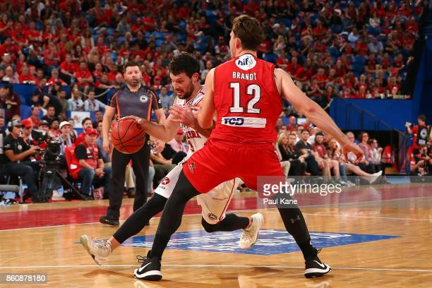 Kevin White of the Hawks drives to the basket against Angus Brandt of the Wildcats during the round two NBL match between the Perth Wildcats and the...