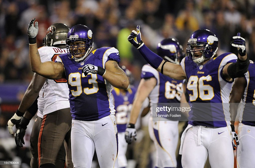 Kevin Williams #93 and Brian Robison #96 of the Minnesota Vikings pump up the crowd during the third quarter of the game against the Tampa Bay Buccaneers on October 25, 2012 at Mall of America Field at the Hubert H. Humphrey Metrodome in Minneapolis, Minnesota.