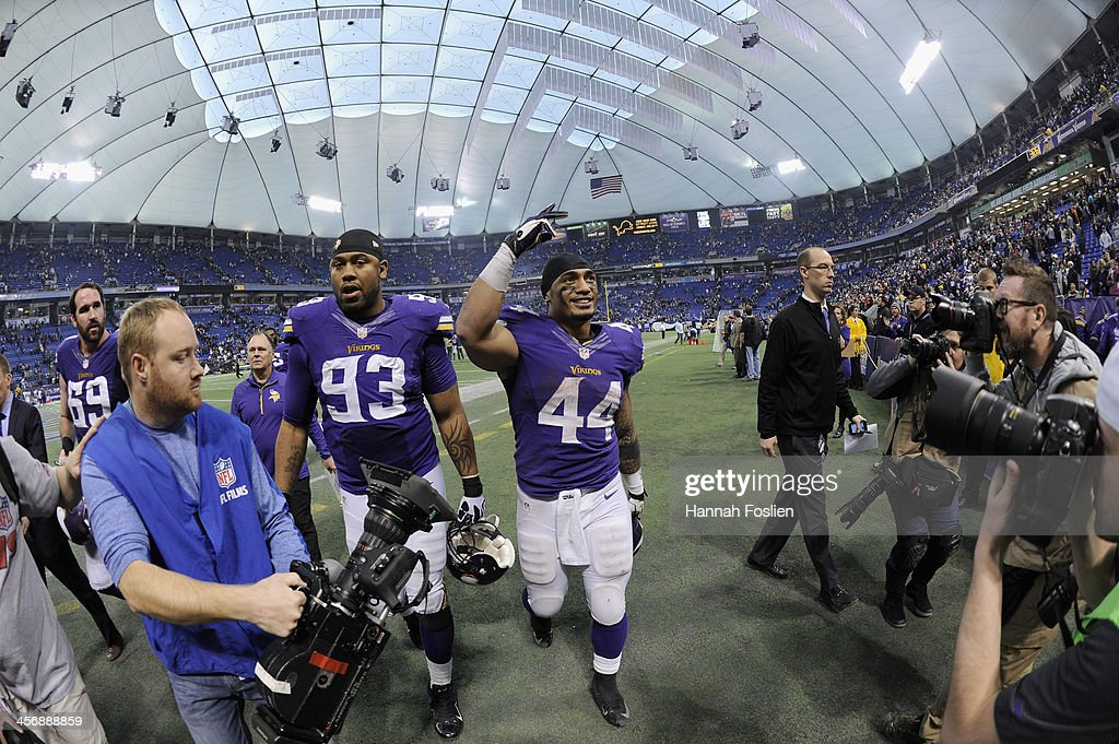 Kevin Williams #93 and Matt Asiata #44 of the Minnesota Vikings walk off the field after a win of the game against the Philadelphia Eagles on December 15, 2013 at Mall of America Field at the Hubert H. Humphrey Metrodome in Minneapolis, Minnesota. The Vikings defeated the Eagles 48-30.