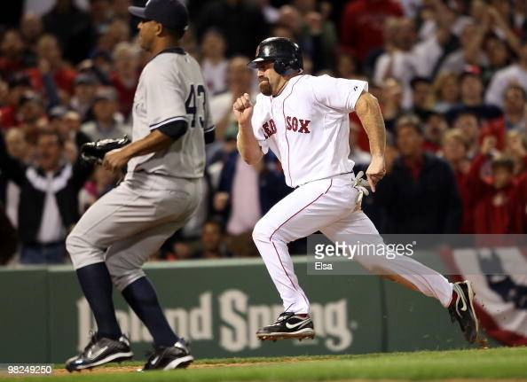 Kevin Youkilis of the Boston Red Sox scores the game winning run as Damaso Marte of the New York Yankees tries to beat him to home plate on April 4...