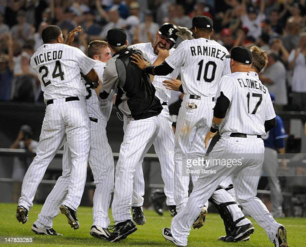 Kevin Youkilis of the Chicago White Sox hits a walk off game winning single in the tenth inning against the Texas Rangers as his teammates celebrate...