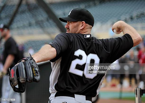Kevin Youkilis of the Chicago White Sox plays catch with a teammate doing batting practice before the game against the Minnesota Twins on June 25...