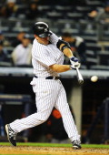 Kevin Youkilis of the New York Yankees hits a single and drives in Brett Gardner for a run against the Baltimore Orioles in the third inning during...