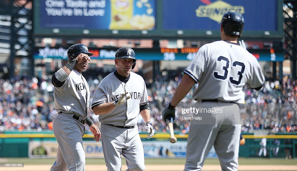 Kevin Youkillis #36 of the New York Yankees celebrates with teammates Robinson Cano #24 and Travis Hafner #33 after hitting a two run home run in the fifth inning during the game against the Detroit Tigers at Comerica Park on April 5, 2013 in Detroit, Michigan.