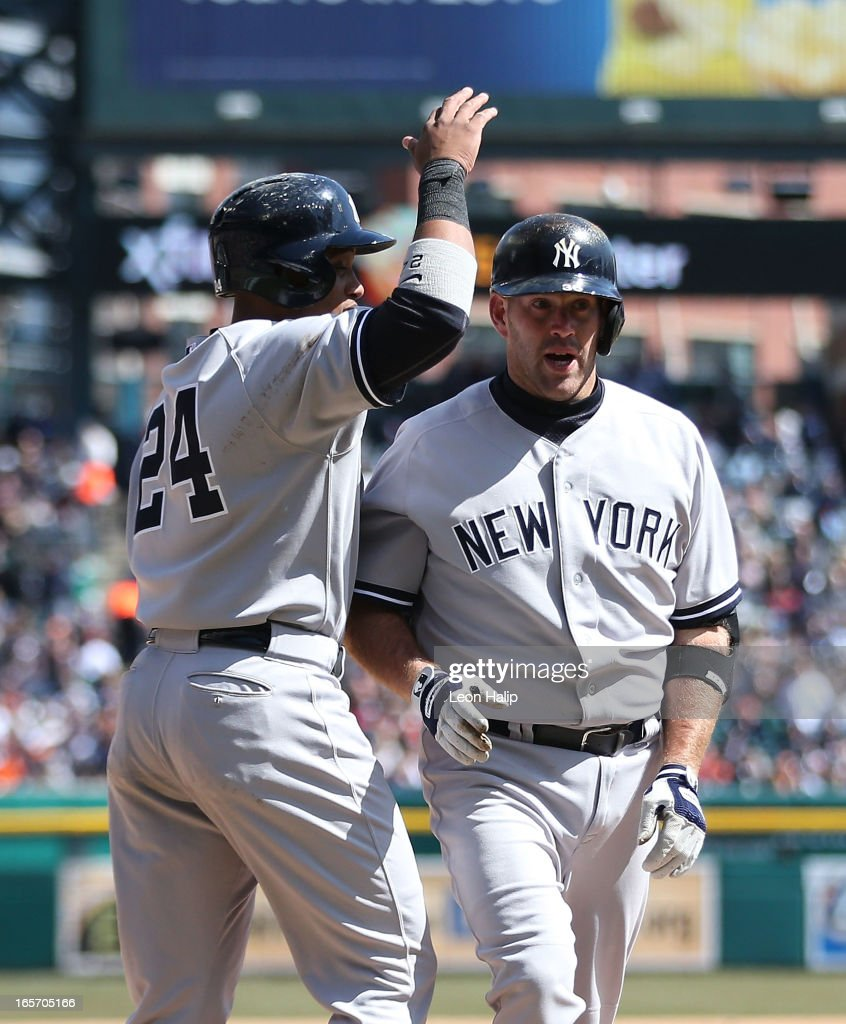 Kevin Youkillis #36 of the New York Yankees celebrates with teammates Robinson Cano #24 after hitting a two run home run in the fifth inning during the game against the Detroit Tigers at Comerica Park on April 5, 2013 in Detroit, Michigan.
