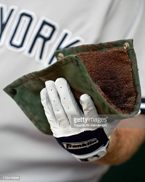 Kevin Youklis of the New York Yankees holds onto the wearing Franklin batting gloves holds onto the pinetar rag in the dugout against the Oakland...