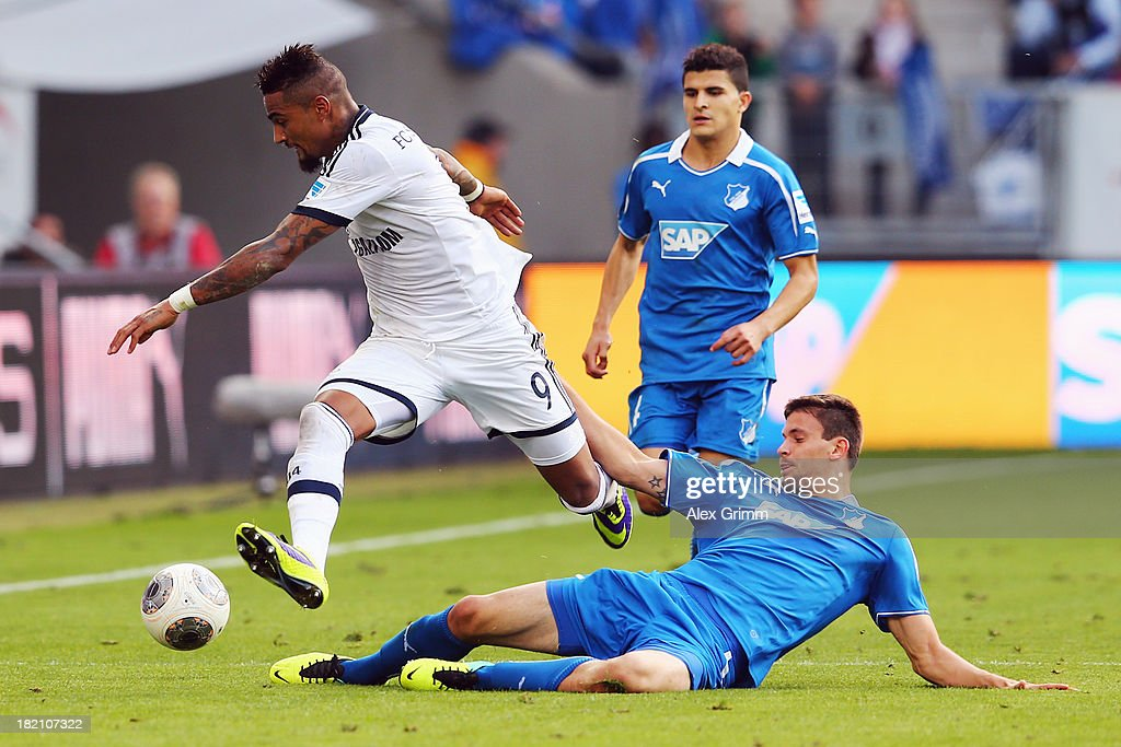 KevinPrince Boateng of Schalke is challenged by Tobias Strobl and Tarik Elyounoussi of Hoffenheim during the Bundesliga match between 1899 Hoffenheim...
