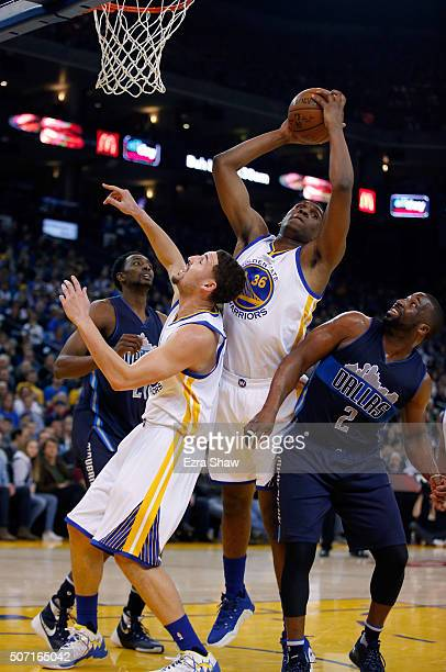 Kevon Looney of the Golden State Warriors grabs a rebound over Klay Thompson of the Golden State Warriors and Raymond Felton of the Dallas Mavericks...