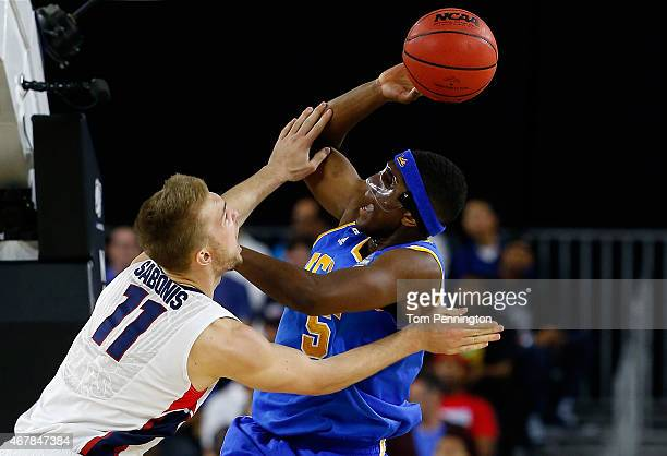 Kevon Looney of the UCLA Bruins drives to the basket as Domantas Sabonis of the Gonzaga Bulldogs defends during a South Regional Semifinal game of...