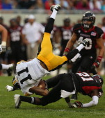 Kevonte MartinManley of the Iowa Hawkeyes is upended by Dechane Durante of the Northern Illinois Huskies at Soldier Field on September 1 2012 in...
