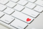 Keyboard with red heart on button, close-up