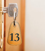 Closeup of an old keyhole of room number 13 with key on a wooden door