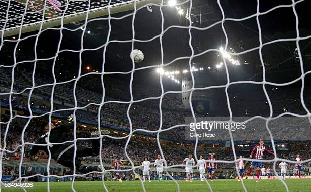 Keylor Navas goalkeeper of Real Madrid looks at the ball as it rebounds off the crossbar as Antoine Griezmann of Atletico Madrid misses a penalty...