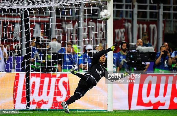 Keylor Navas of Real Madrid dives as Antoine Griezmann of Atletico Madrid penalty hits the woodwork during the UEFA Champions League Final between...