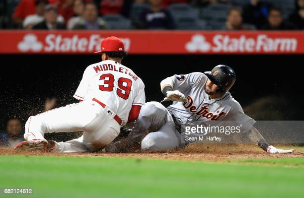 Keynan Middleton of the Los Angeles Angels of Anaheim tags out Nicholas Castellanos of the Detroit Tigers as he tries to steal home on a wild pitch...
