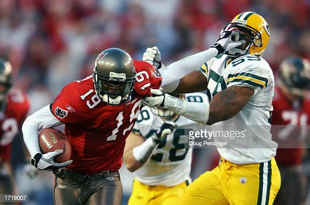 Keyshawn Johnson of the Tampa Bay Buccaneers grabs a 39 yard pass and tries to fend off Na'il Diggs of the Green Bay Packers as it sets up a second...