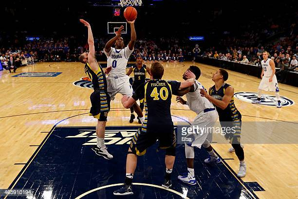 Khadeen Carrington of the Seton Hall Pirates goes up for a shot as Matt Carlino of the Marquette Golden Eagles defends during a first round game of...