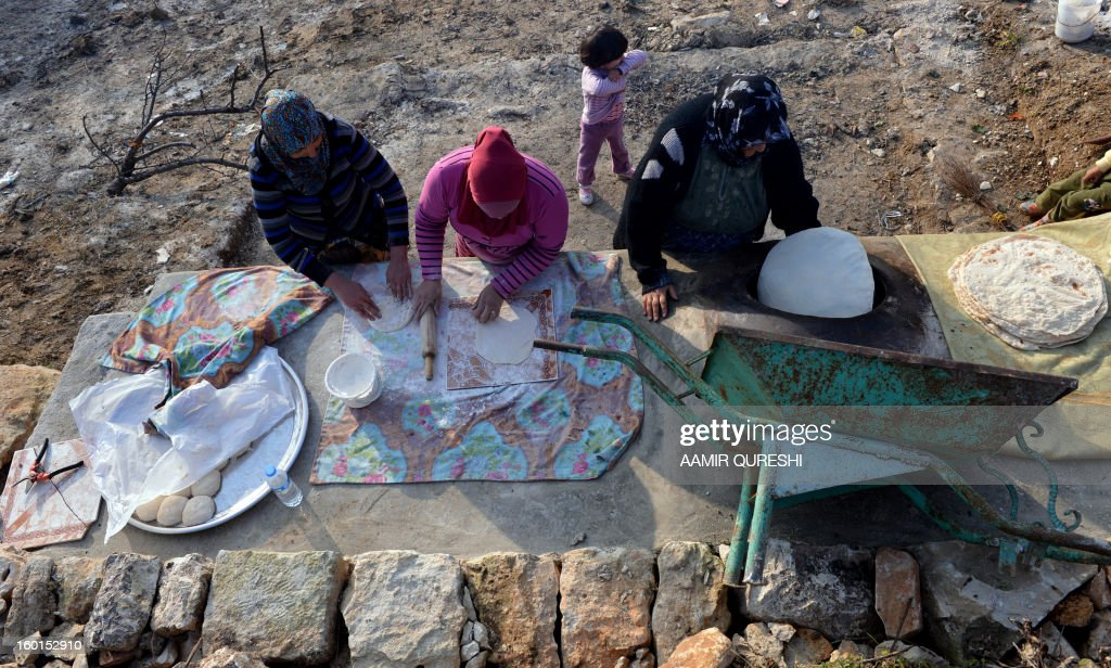 Khadija (R), a 75-year-old Kurdish woman who evacuated her home due to shelling by Syrian regime forces, bakes bread with other displaced women outside a borrowed house in Khirbet Al-Joz, in the northwestern Syrian province of Idlib on January 22, 2013. In the green, mountainous part of northwest Syria, the boom of shells vibrate every few hours through dozens of villages abandoned by their terrified Kurdish inhabitants. AFP PHOTO/AAMIR QURESHI