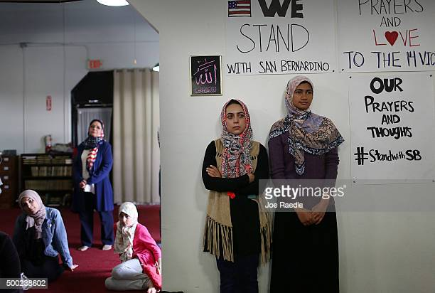 Khadija Zadeh and Noora Siddiqui stand together as they attend an interfaith service at the Islamic Community Center of Redlands for the victims of...