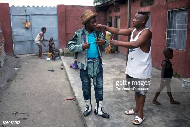 Khaditoza Gola the leader of the Leopard Sapeur helps his son Khaditoza Exauce age 16 to dress at their home on February 12 2017 in Kinshasa DRC The...