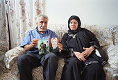Khadra Elkhra and her husband Lutfi Elkhra sit together as Lutfi holds pictures of their daughter July 25 2002 in Bethlehem West Bank The pictures...