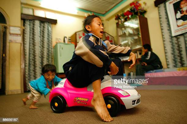 Khagendra Thapa Magar 15 and a half pushes family friend Sabina around the living room on a toy car on March 13 2007 in Pokhara Nepal According to...