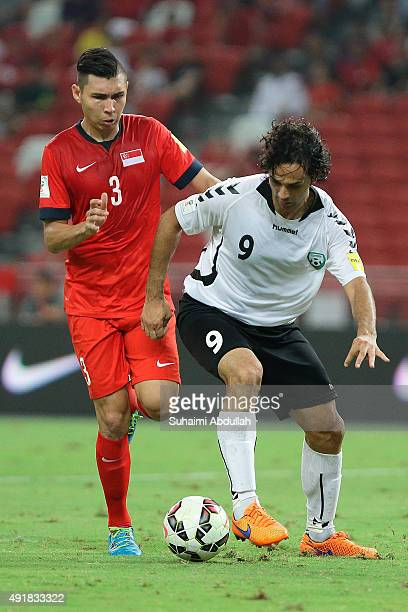 Khaibar Amani of Afghanistan dribbles past Mohamad Shaiful Bin Esah Nain of Singapore during the FIFA 2018 World Cup Qualifier match between...