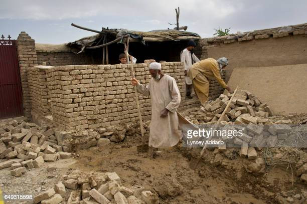 Khalahuddin helps his son and nephew build a kitchen on the grounds of his home in the mostly abandoned land allocation settlement of AliceGhan about...