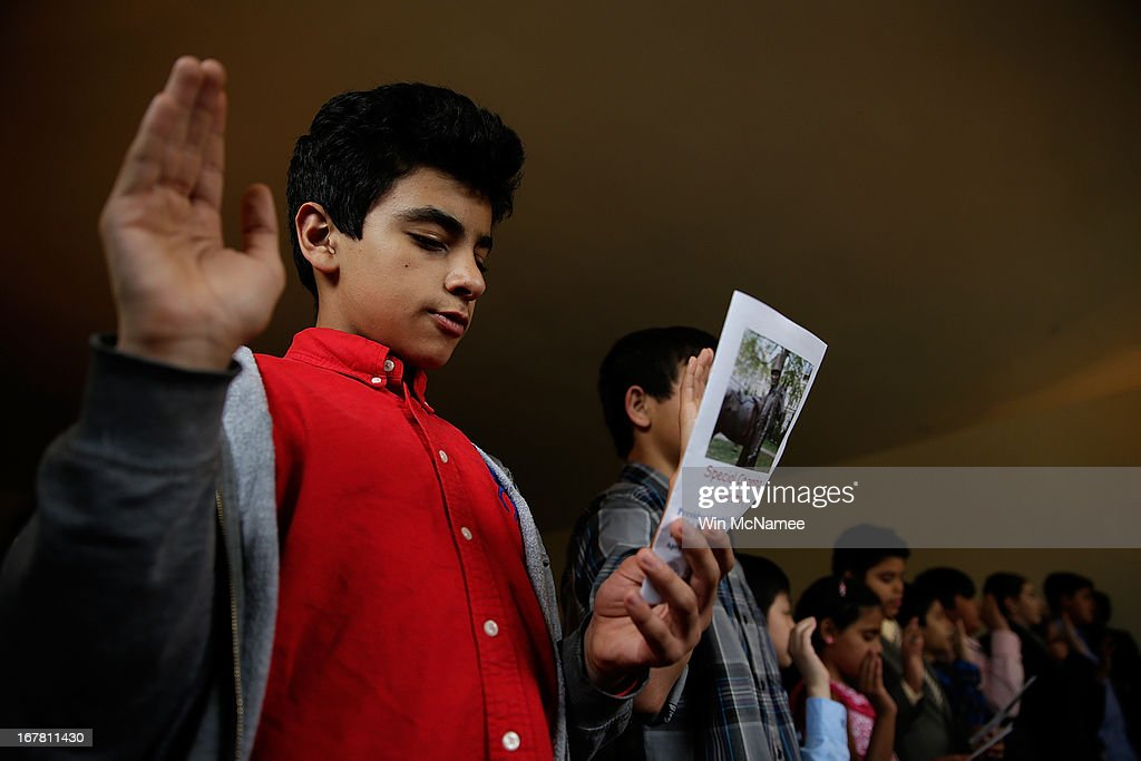 Khaldon Al Shawkani (L) joins other children in taking the Oath of Allegiance during a naturalization ceremony in the Emancipation Room at President Abraham Lincoln's Cottage April 30, 2013 in Washington, DC. The special citizenship ceremony for twenty children was hosted by the U.S. Citizen and Immigration Services at the seasonal residence the Lincoln family used during the Civil War and the site where President Lincoln developed the Emancipation Proclamation.