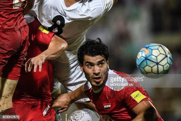 TOPSHOT Khaled Almbayed of Syria heads the ball against Morteza Pouraliganji of Iran during the 2018 World Cup qualifying football match between...