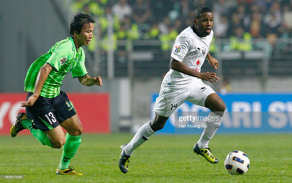 Khalfan Ibrahim of Al Sadd and Jung Hoon of Jeonbuk Hyundai Motors compete for the ball during the AFC Champions League Final Match between Jeonbuk Hyundai Mortors of South Korea and Al Sadd of Qatar at Jeonju World Cup Stadium on November 05, 2011 in Jeonju, South Korea. Al Sadd won the Match against Jeonbuk Hyundai Motors.