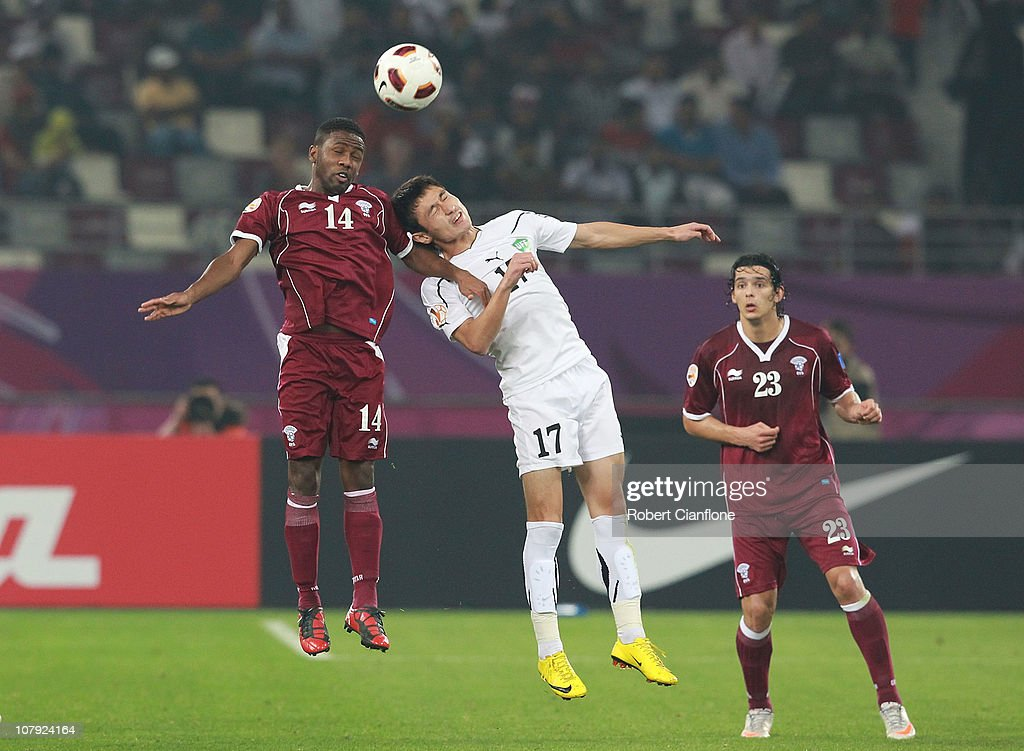 Khalfan Ibrahim of Qatar and Sanjar Tursunov of Uzbekistan challenge eachother for the ball during the AFC Asian Cup Group A match between Qatar and Uzbekistan at Khalifa Stadium on January 7, 2011 in Doha, Qatar.