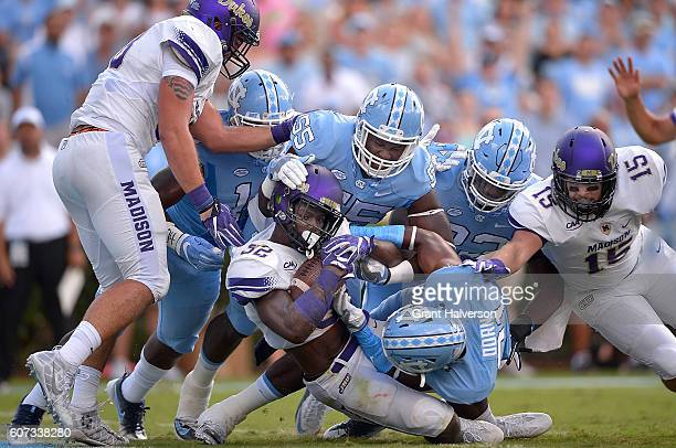 Khalid Abdullah of the James Madison Dukes drives through Jason Strowbridge and Myles Dorn of the North Carolina Tar Heels for a touchdown during the...